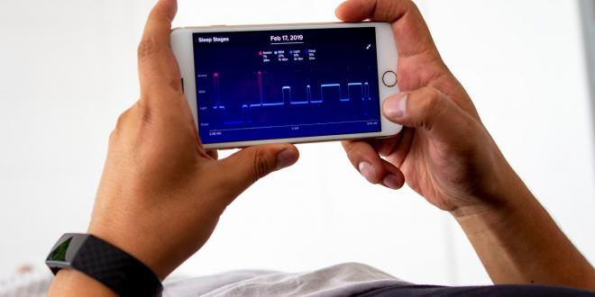 Man laying  monitoring his sleep night with app.