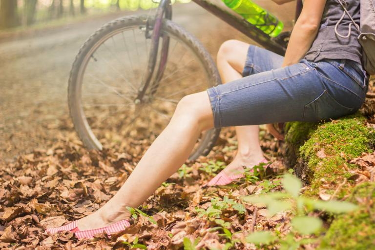 a woman with smooth calves sitting next to her bicycle